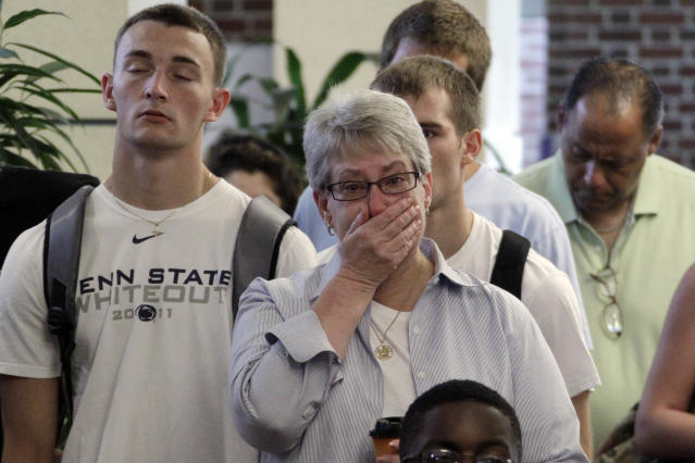 Susan DelPonte, center, of State College, Pa., reacts to a television in the HUB on the Penn State University main campus in State College, Pa., as the NCAA sanctions against the Penn State University football program are announced Monday, July 23, 2012. (AP Photo/Gene J. Puskar)