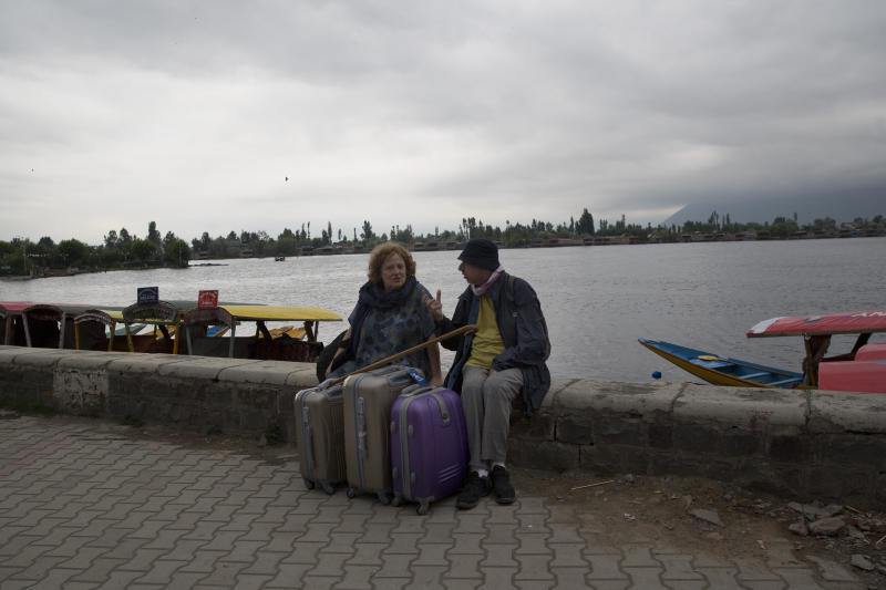 """An Italian couple wait for their taxi as they prepare to leave Srinagar, Indian controlled Kashmir, Saturday, Aug. 3, 2019. A government order in Indian-administered Kashmir on Friday asked tourists and Hindu pilgrims visiting a Himalayan cave shrine """"to curtail their stay"""" in the disputed territory, citing security concerns and intensifying tensions following India's announcement it was sending more troops to the region. (AP Photo/ Dar Yasin)"""