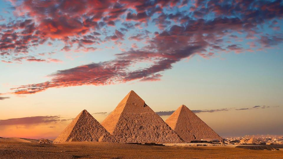 """<p>The Great Pyramids of Giza are one of the world's seven ancient wonders. Amid the arid Egyptian desert stands a complex of massive pyramids that once <a href=""""https://www.britannica.com/topic/Pyramids-of-Giza"""" rel=""""nofollow noopener"""" target=""""_blank"""" data-ylk=""""slk:served as the tombs"""" class=""""link rapid-noclick-resp"""">served as the tombs</a> for powerful rulers of the 4th dynasty (c. 2575–c. 2465 BCE) - King Khufu, King Khafre, and King Menkaure. The mysterious landmarks are mighty architectural achievements that capture the attention of millions of visitors each year, and as the oldest standing monuments in the world, it's no wonder why. Embark on a virtual journey to Egypt and discover these facts about the Great Pyramids of Giza.</p>"""