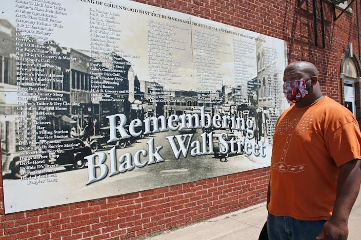 Freeman Culver in front of a mural on Monday listing the names of businesses destroyed during the 1921 race massacre in Tulsa, Oklahoma.