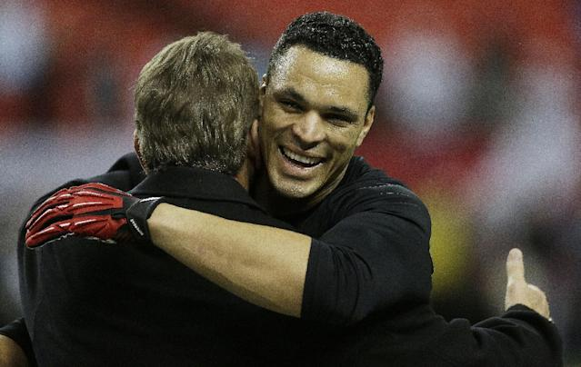 Atlanta Falcons tight end Tony Gonzalez, right, speaks with former NFL football player Joe Theismann speaks with works out before the first half of an NFL football game Carolina Panthers, Sunday, Dec. 29, 2013, in Atlanta. Gonzales possibly plans to retire after this season. (AP Photo/John Bazemore)