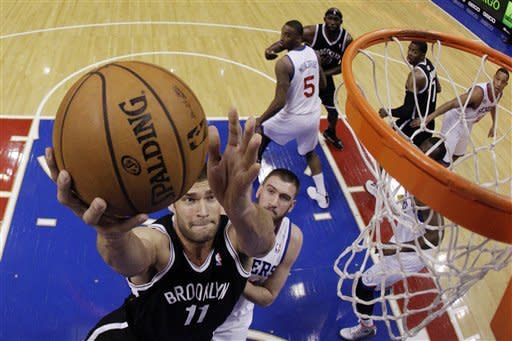 Brooklyn Nets' Brook Lopez, left, shoots as Philadelphia 76ers' Spencer Hawes defends in the first half of an NBA basketball game, Monday, March 11, 2013, in Philadelphia. (AP Photo/Matt Slocum)