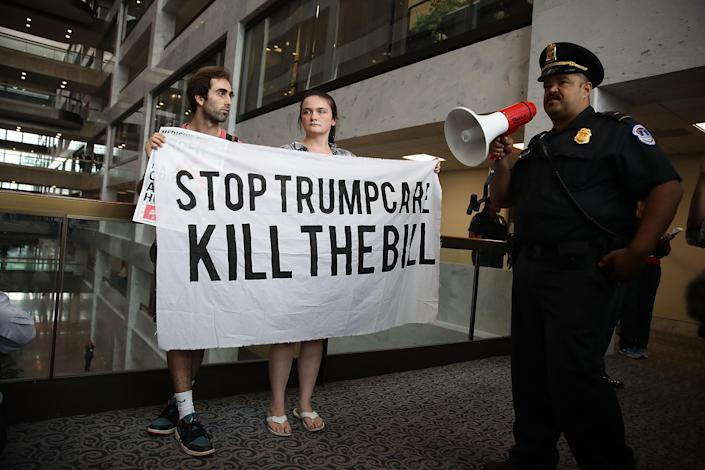 A U.S. Capitol Police officer asks protesters to leave the area around the office of Sen. Dean Heller, R-Nev., as they voice their opinion about the proposed health care bill in the Hart Senate Office Building on July 17, 2017, in Washington, D.C. Capitol Police arrested several protesters at various Senate offices as they asked senators to vote no on the Better Care Reconciliation Act. (Photo: Joe Raedle/Getty Images)