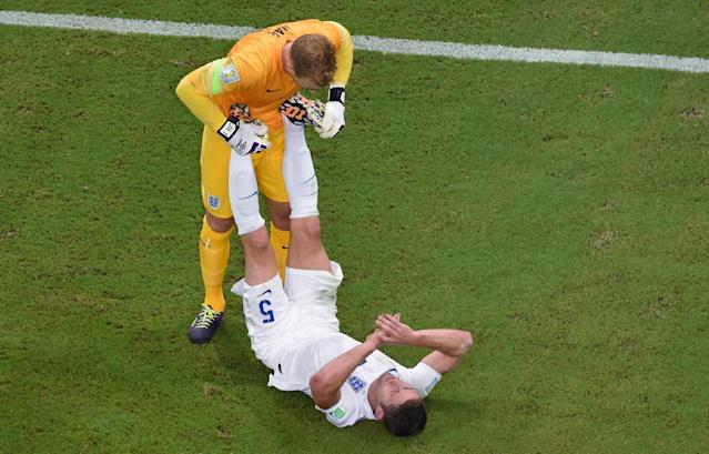England's goalkeeper Joe Hart, left, stretches the calve muscles of his teammate Gary Cahill during the group D World Cup soccer match between England and Italy at the Arena da Amazonia in Manaus, Brazil, Saturday, June 14, 2014. (AP Photo/Francois Xavier Marit, pool)