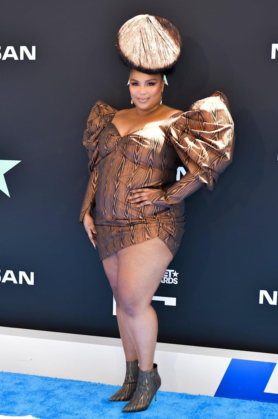Lizzo shut down the BET blue carpet when she turned up wearing a brown mini dress from House of Holland with exaggerated shoulders and a matching hat.