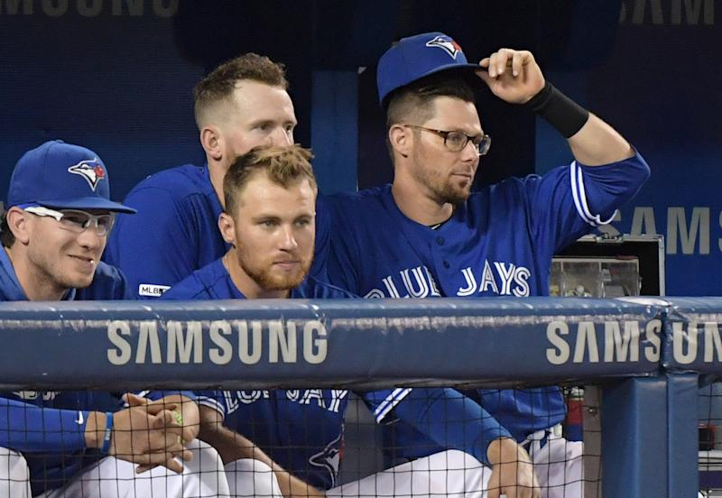 Jul 28, 2019; Toronto, Ontario, CAN; Toronto Blue Jays former infielder Eric Sogard (5) tips his cap as he bids farewell to former teammates catcher Danny Jansen (left) and right fielder Billy McKinney (obscured) and third baseman Brandon Drury after being traded to Tampa Bay Rays in the third inning during a game against the Rays at Rogers Centre. Mandatory Credit: Dan Hamilton-USA TODAY Sports