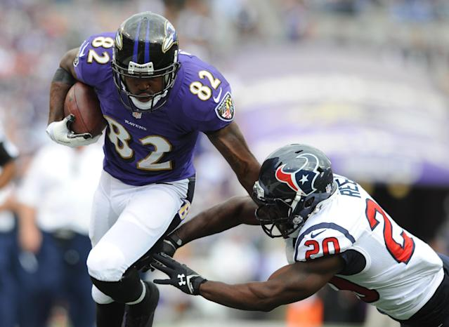 Baltimore Ravens wide receiver Torrey Smith, left, rushes past Houston Texans free safety Ed Reed in the second half of an NFL football game Sunday, Sept. 22, 2013, in Baltimore. (AP Photo/Gail Burton)
