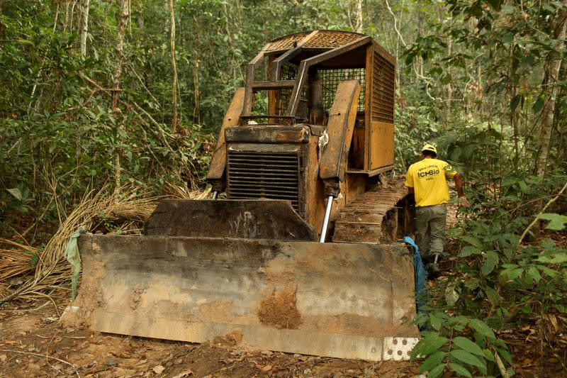 FILE PHOTO: FILE PHOTO: A member of the Chico Mendes Institute for Biodiversity Conservation (ICMBio) walks next a tractor used for deforestation at the National Forest Bom Futuro in Rio Pardo
