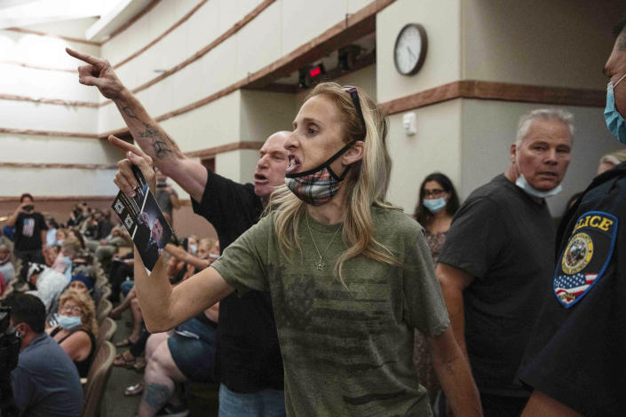 FILE - In this Aug. 12, 2021, file photo, protesters against a COVID-19 mandate gesture as they are escorted out of the Clark County School Board meeting at the Clark County Government Center, in Las Vegas. A growing number of school board members across the U.S. are resigning or questioning their willingness to serve as meetings have devolved into shouting contests over contentious issues including masks in schools. (Bizuayehu Tesfaye/Las Vegas Review-Journal via AP, File)