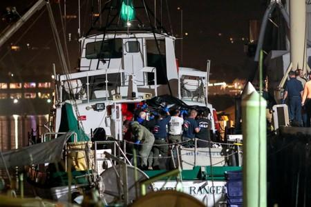 FILE PHOTO: Rescue personnel return to shore with the victims of a pre-dawn fire that sank a commercial diving boat off the coast of  Santa Barbara, California