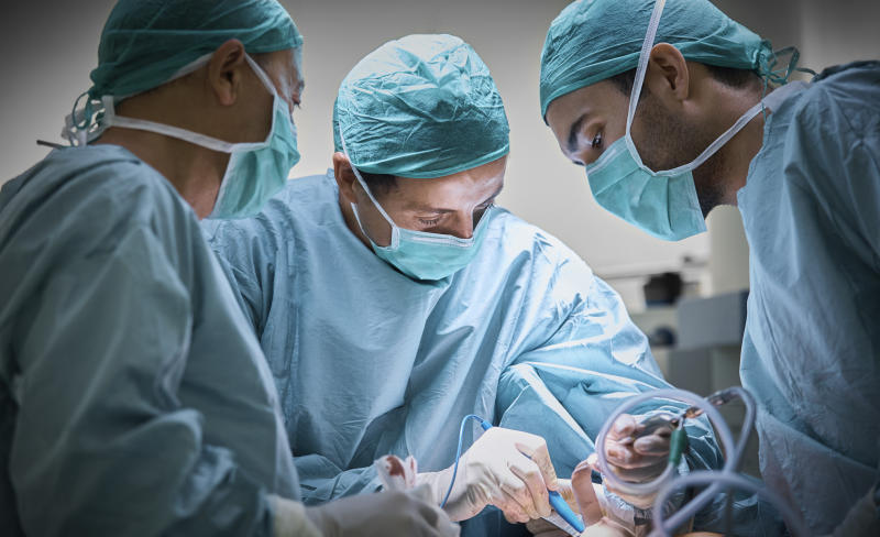 Plastic surgeons operating patient for breast implant. Team of doctors are in scrubs at operating room. They are at hospital.