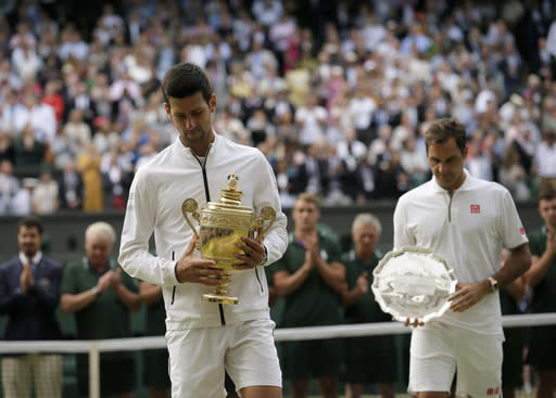 Serbia's Novak Djokovic and Switzerland's Roger Federer walk with the trophies after the men's singles final match of the Wimbledon Tennis Championships in London, Sunday, July 14, 2019. (AP Photo/Tim Ireland)