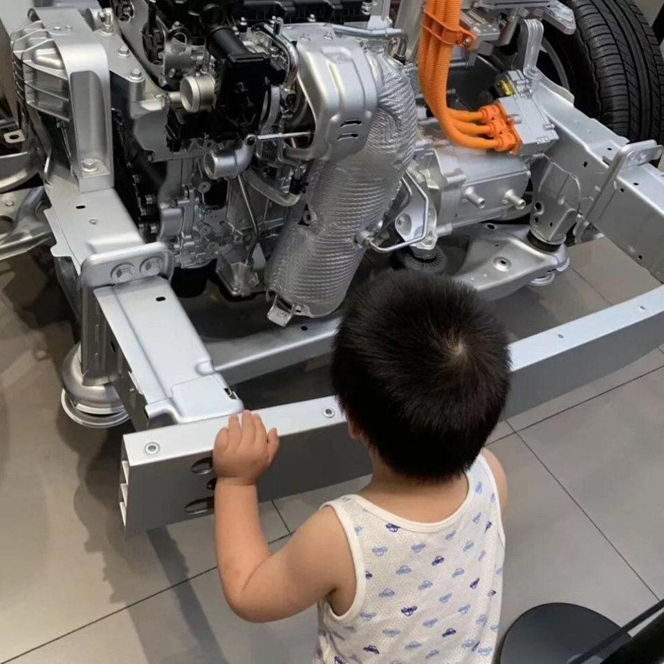 Chris Zou's now four-year-old son Xinxin, looking at the chassis and engine of a car, in Shanghai, China. Photo: Chris Zou
