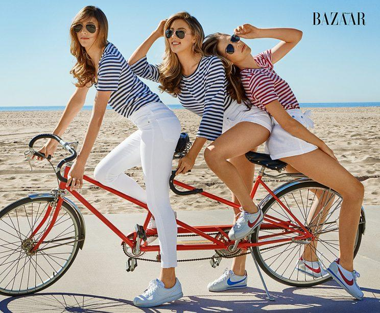 Scarlet, Sistine, and Sophia Stallone on a tandem bike on the beach.