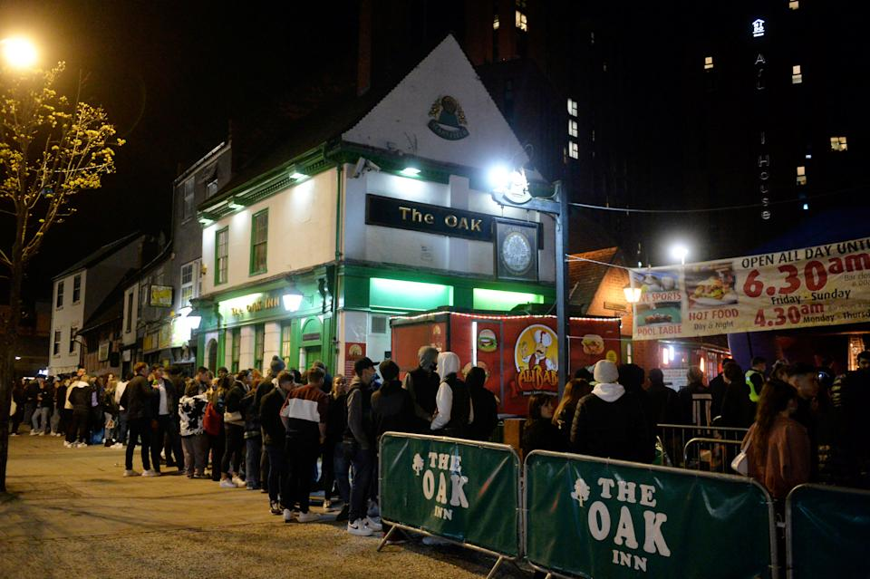 People queueing outside The Oak Inn in Coventry, hoping to enjoy their first post-lockdown pints mere moments after midnight as restrictions across the UK are partially eased. The establishment is licensed till 6am, and also plans to sell food throughout the night, such as pizzas, burgers and kebabs. April 11 2021.