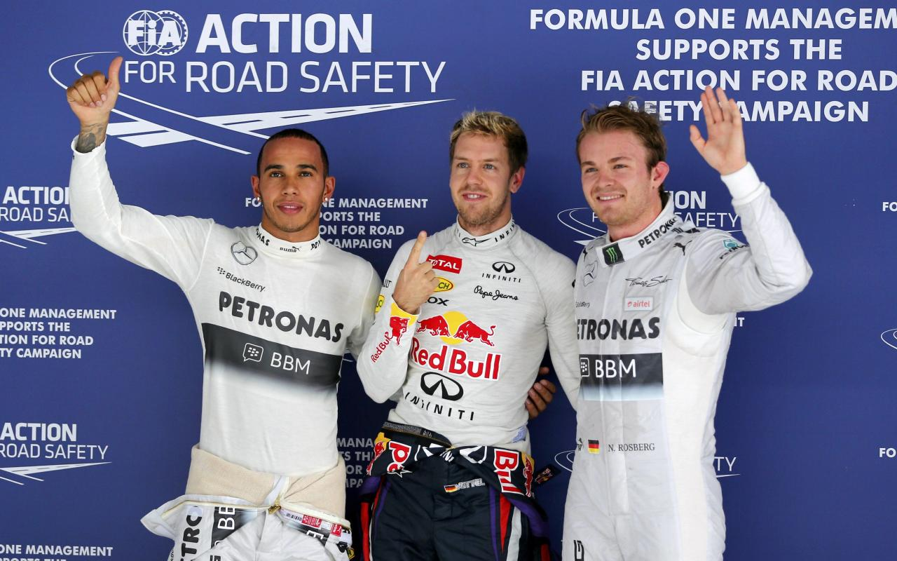 (L-R) Mercedes Formula One driver Lewis Hamilton of Britain, Red Bull Formula One driver Sebastian Vettel of Germany and Mercedes Formula One driver Nico Rosberg of Germany pose for photographers after the qualifying session of the Indian F1 Grand Prix at the Buddh International Circuit in Greater Noida, on the outskirts of New Delhi, October 26, 2013. Vettel put himself on pole position for a fourth successive Formula One title after lapping the Indian Grand Prix circuit faster than ever before on Saturday. REUTERS/Ahmad Masood (INDIA - Tags: SPORT MOTORSPORT F1)