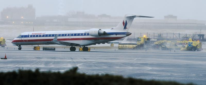 Grounds crews pass a plane as they clear the tarmac at LaGuardia Airport Friday, Feb. 8, 2013, in New York. A blizzard of potentially historic proportions threatens to strike the Northeast with 1 to 2 feet of snow forecast along the densely populated Interstate 95 corridor from New York City to Boston and beyond. (AP Photo/Frank Franklin II)
