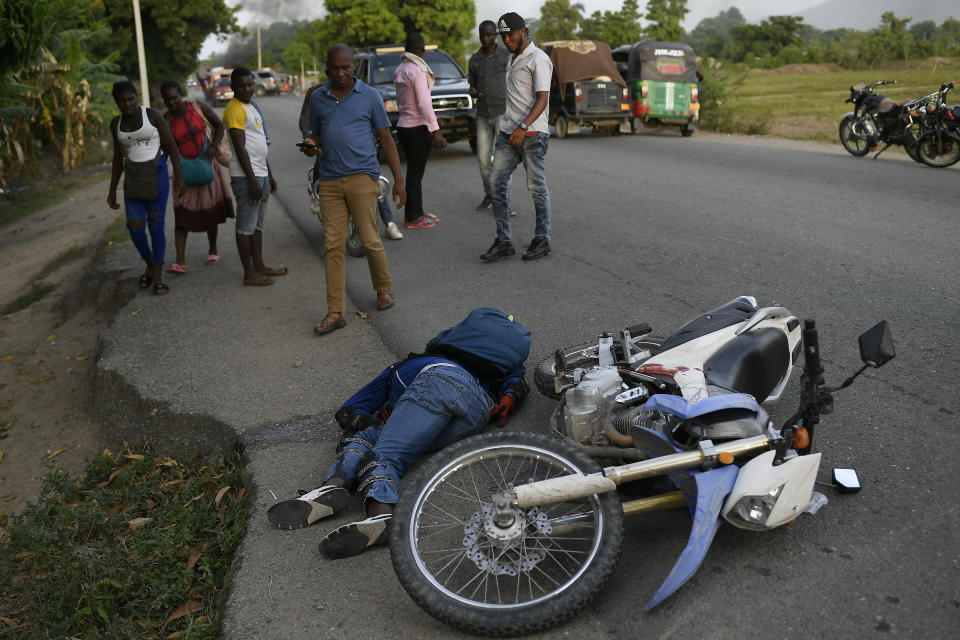 A man lies dead on the road after violence broke out and hundreds of workers fled the area when demonstration near the home town of late President Jovenel Moise grew violent, ahead of his funeral in Quartier Morin a district of Cap Haitien, in northern Haiti, Wednesday, July 21, 2021. (AP Photo/Matias Delacroix)