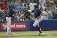 Boston Red Sox's Xander Bogaerts, right, is congratulated by third base coach Carlos Febles (52) after his solo home run against the Tampa Bay Rays during the third inning of Game 2 of a baseball American League Division Series, Friday, Oct. 8, 2021, in St. Petersburg, Fla. (AP Photo/Chris O'Meara)