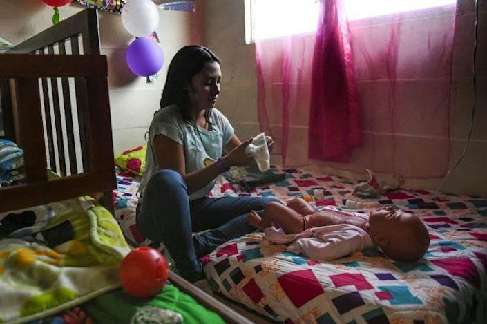 Susana Ortegon takes care of baby Anthony at her home (AFP Photo/JOAQUIN SARMIENTO)