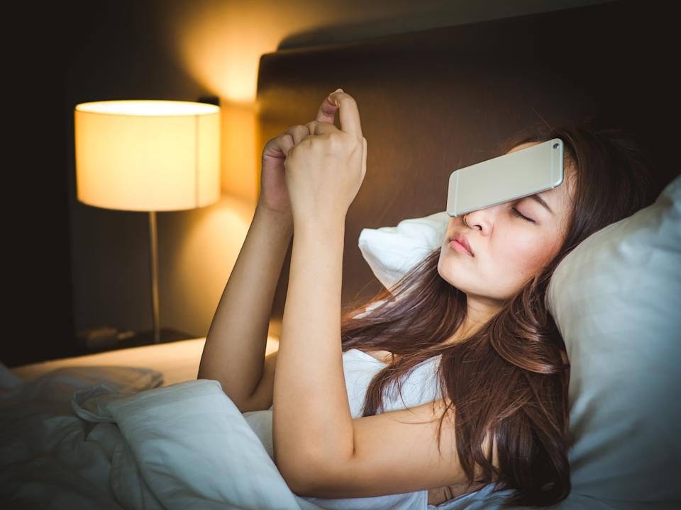 Sleepy asian woman in white bed, dropped smart phone on face