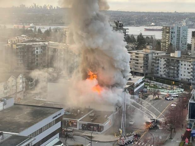 Flames engulf a building near Lonsdale Avenue and 12th Street in North Vancouver on Tuesday.