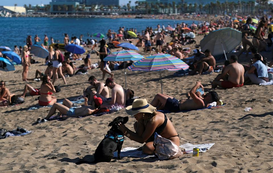 People enjoy the sunny weather at Barceloneta beach, after Catalonia's regional authorities and the city council announced restrictions to contain the spread of the coronavirus disease (COVID-19) in Barcelona, Spain July 19, 2020. REUTERS/Nacho Doce