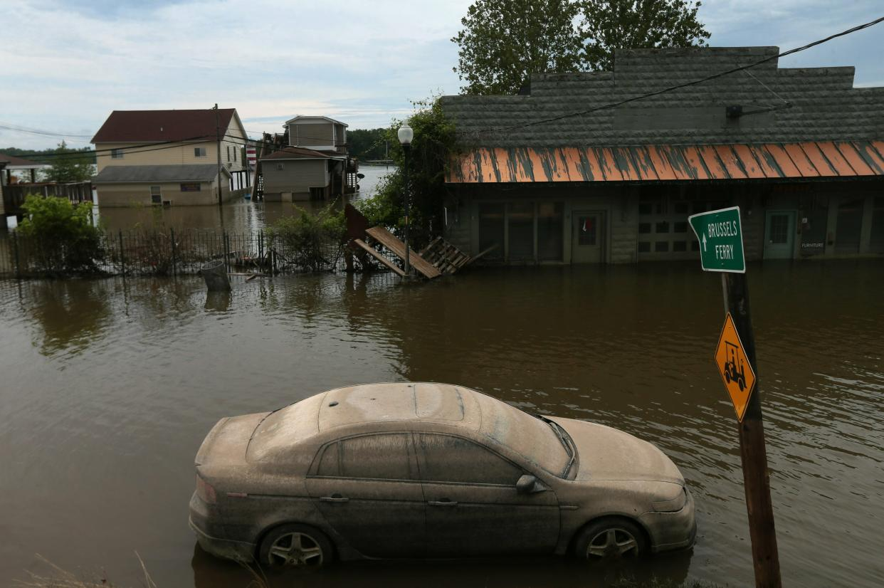 A lone car, once submerged in flood waters, sits caked in mud along Main Street on Wednesday, June 19, 2019, in Grafton, Ill. On Wednesday, the level of the Mississippi River was 30.2 feet, having dropped about five feet from its crest at 35.17 on June 7. (Photo: Laurie Skrivan/St. Louis Post-Dispatch via AP)