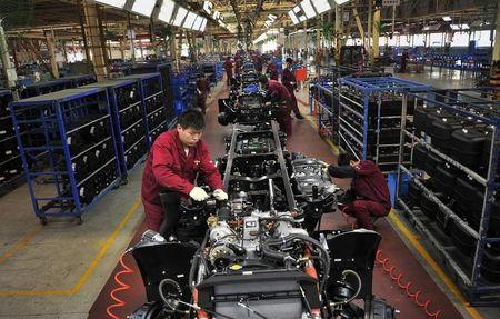 Workers install the chassis along a production line at a truck factory of Anhui Jianghuai Automobile Co. Ltd (JAC Motors) in Hefei