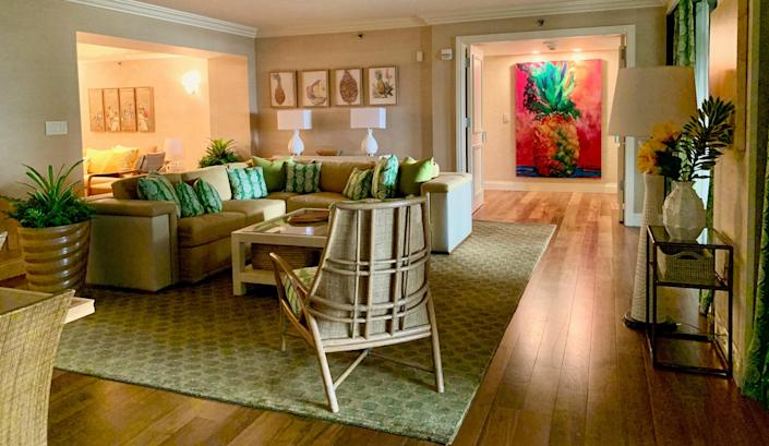 The Pineapple Suite employs earth tones of yellow, green, and brown and incorporates the pineapple motif on pillow covers and curtains.
