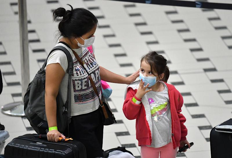 A mother and her daughter who are amongst a group of Australians evacuated from South America due to the COVID-19 pandemic are seen after landing at Brisbane International Airport in Brisbane, Tuesday, April 14, 2020. A Qantas flight from Lima, repatriated 115 passengers back to Australia. AAP Image