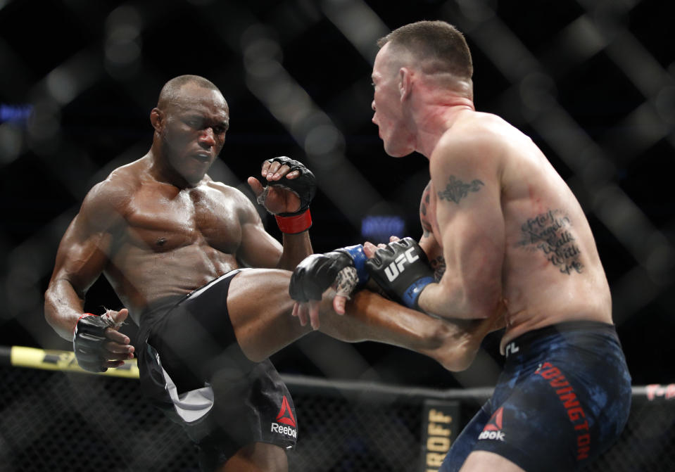 "FILE - Kamaru Usman kicks Colby Covington in a mixed martial arts welterweight championship bout at UFC 245 in Las Vegas, in this Saturday, Dec. 14, 2019, file photo. UFC 261 is being touted as the first full-capacity sporting event held indoors in more than a year. The card features three title fights, highlighted by a rematch between reigning welterweight champion Kamaru ""Nigerian Nightmare"" Usman (18-1) and Jorge ""King of Miami"" Masvidal (35-14). (AP Photo/John Locher, File)"