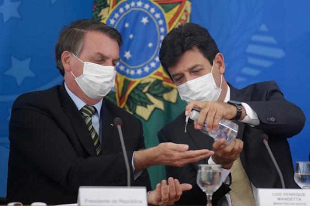 BRASILIA, BRAZIL - MARCH 18: Brazilian Health Minister Luiz Henrique Mandetta (R) gives gel alcohol to President of Brazil Jair Bolsonaro, both using protective masks, during a press conference regarding government plans and measures on Coronavirus (COVID-19) Outbreak in Brazil, at the Planalto Palace on March 18, 2020 in Brasilia, Brazil. (Photo by Andre Coelho/Getty Images)