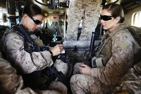 US Marine and Female Engagement Team leader Sgt. Adams and H.N. Crowley sit in armoured vehicle before heading out on an operation in Helmand province