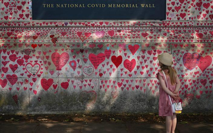 A child looking at the National Covid Memorial Wall on the Embankment in London, - Yui Mok/PA