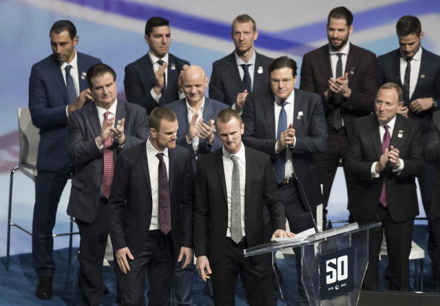 Retired Vancouver Canucks players. twins Daniel, front left, and Henrik Sedin, prepare to speak during a jersey retirement ceremony before an NHL hockey game between the Canucks and the Chicago Blackhawks in Vancouver, British Columbia, Wednesday Feb. 12, 2020. (Darryl Dyck/The Canadian Press via AP)