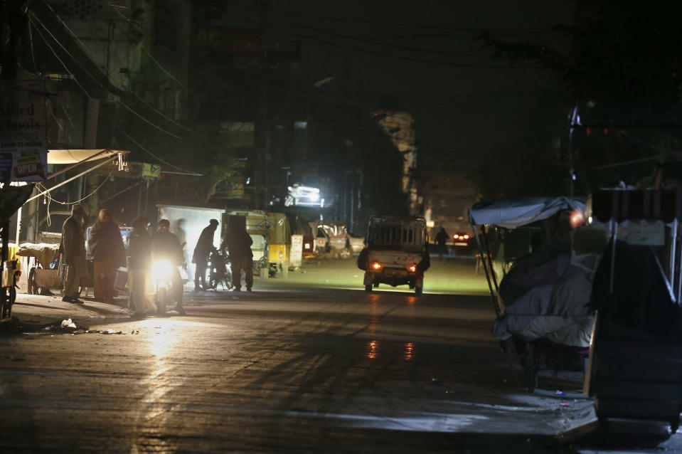 People are silhouetted on a vehicle headlights on a dark street during widespread power outages in Rawalpindi, Pakistan, Sunday, Jan. 10, 2021. Pakistan's national power grid experienced a major breakdown late night on Saturday, leaving millions of people in darkness, local media reported. (AP Photo/Anjum Naveed)