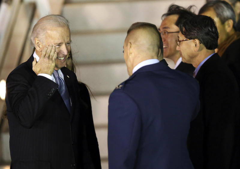 U.S. Vice President Joe Biden, left, salutes to U.S. Air Force Col. Brook Leonard, right, upon his arrival at Osan Air Base in Osan, South Korea, Thursday, Dec. 5, 2013. (AP Photo/Ahn Young-joon)