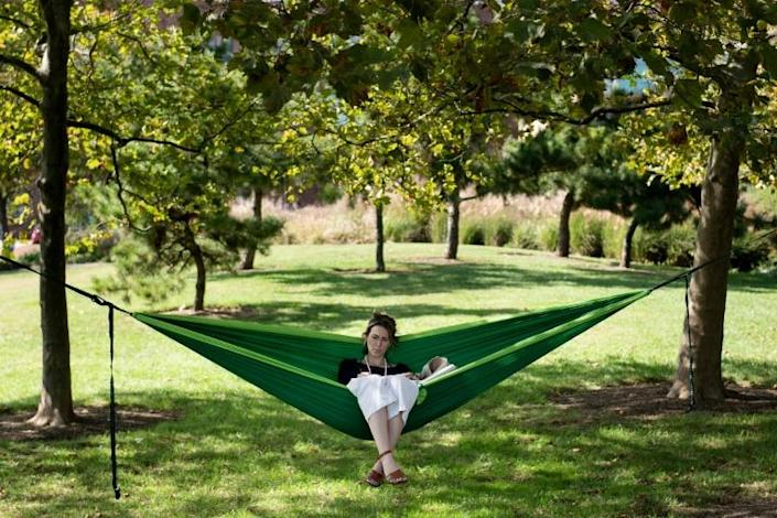 Cait McKay sits in a hammock in Baltimore's Canton neighborhood, one of the city's wealthiest areas