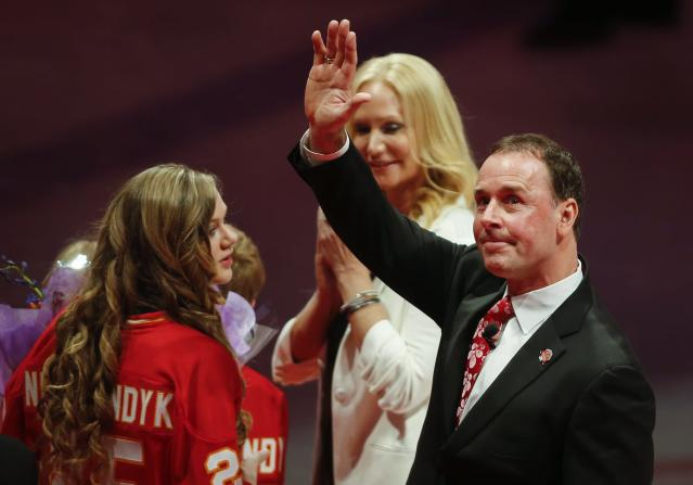 Former Calgary Flames great Joe Nieuwendyk, right, stands with his family as he waves to fans following a ceremony honoring him before the Flames' NHL hockey game against the New York Islanders in Calgary, Alberta, Friday, March 7, 2014. (AP Photo/The Canadian Press, Jeff McIntosh)