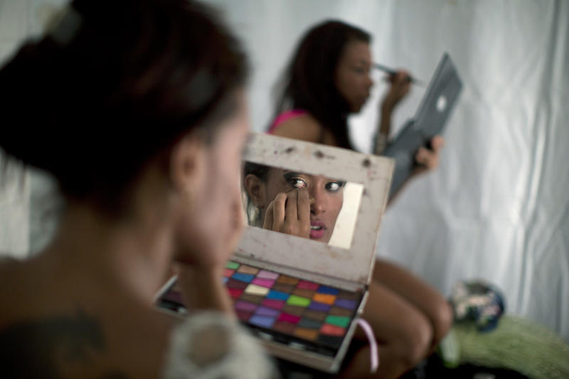 In this photo taken Saturday, Feb. 2, 2013, samba dancer Diana Prado looks in a makeup mirror as applies makeup before the start of a carnival parade at central station in Rio de Janeiro, Brazil. Prado made her Carnival debut at age 19, after auditioning for a spot with the Sao Clemente, one of 13 top-tier schools that will compete for the annual titles at the Sambadrome this weekend. (AP Photo/Felipe Dana)