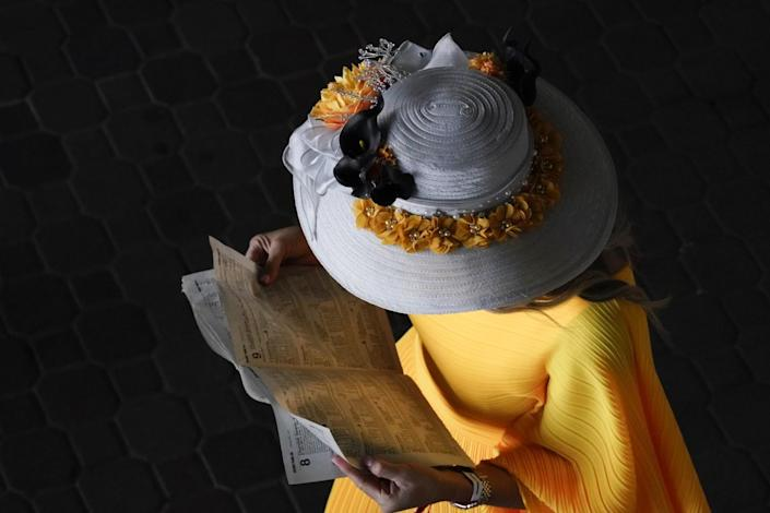 A woman wears a gray brimmed hat with yellow flowers around the brim and a yellow dress.