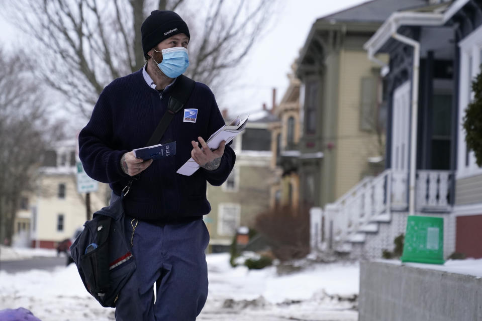 Postal carrier Josiah Morse makes his rounds, Wednesday, Feb. 3, 2021, in Portland, Maine. The U.S. Postal Service's stretch of challenges didn't end with the November general election and tens of millions of mail-in votes. The pandemic-depleted workforce fell further into a hole during the holiday rush, leading to long hours and a mountain of delayed mail. (AP Photo/Robert F. Bukaty)