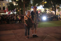 A couple with flowers stand in silence in front of the Cenotaph as they gather to celebrate the 74th Anniversary of the Liberation of Hong Kong, Friday, Aug. 30, 2019, in Hong Kong. Police have appealed to Hong Kong residents to stay from any non-authorized rallies on Saturday after authorities banned a major march, warning that those caught could face a five-year jail term. (AP Photo/Jae C. Hong)