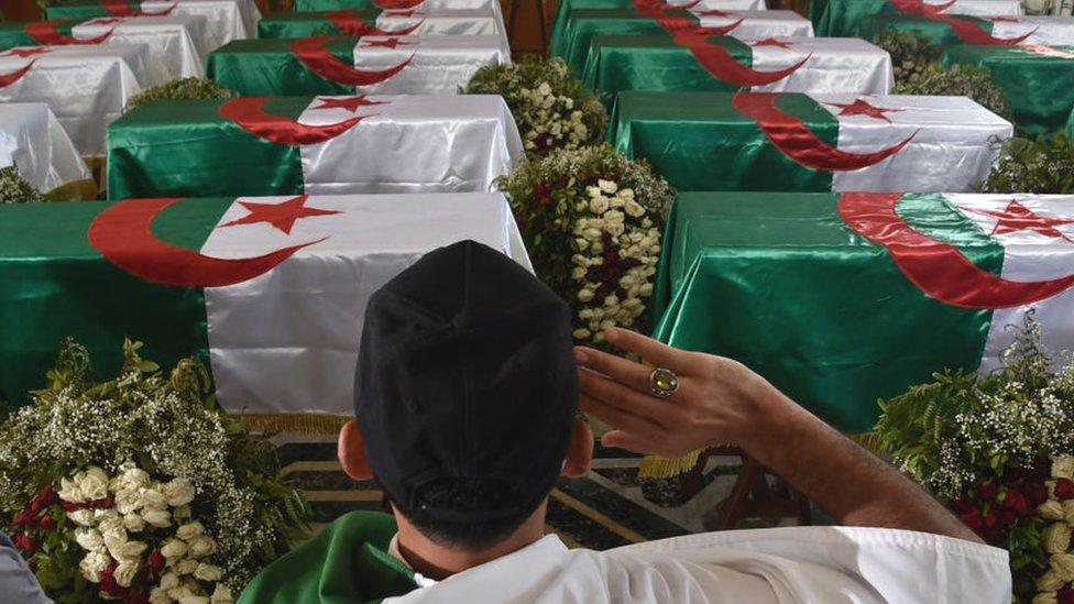An Algerian man pays respect in front of the national flag-draped coffins containing the remains of 24 Algerian resistance fighters at the Palais De La Culture Moufdi Zakaria a day after they were flown in from France - July 2020