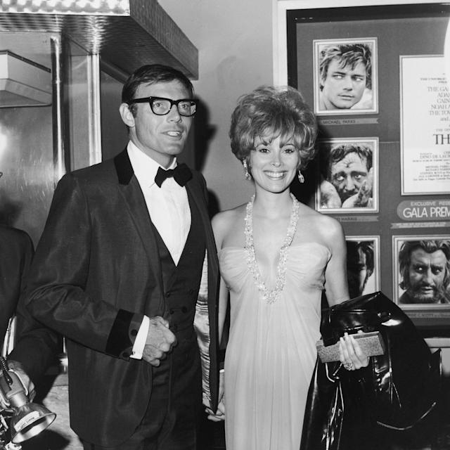 "<p>Adam West and Jill St. John smile and hold hands at the premiere of director John Huston's film, ""The Bible,"" Oct. 1966.' They are standing in front of a billboard advertising the film. (Photo: Max B. Miller/Fotos International/Getty Images) </p>"