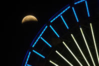 <p>The lunar eclipse shines behind a Ferris wheel in Santa Monica, Calif., Wednesday, May 26, 2021. The first total lunar eclipse in more than two years is coinciding with a supermoon for quite a cosmic show. (AP Photo/Ringo H.W. Chiu)</p>