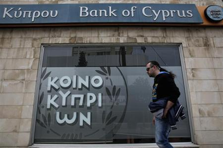 Man walks past a branch of Bank of Cyprus in Nicosia