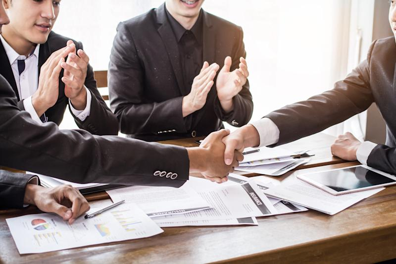 Men in suits shaking hands over a table covered in papers