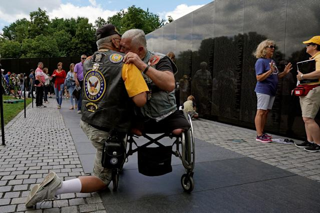 <p>In town for the Memorial Day weekend, Vietnam War veterans Jim Corrales (L) of Fontana, California and Mike Hodge of Seattle, Washington, comfort one another in front of the Vietnam Veterans Memorial in Washington, U.S., May 26, 2017. (Photo: Kevin Lamarque/Reuters) </p>